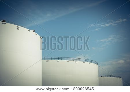 Oil tanks in a row under blue sky in Pasadena, Texas, USA. Large white industrial tank for petrol, oil, natural gas storage. Tank farm at petrochemical, oil refinery plant. Energy and power. Vintage