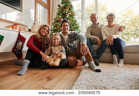 Portrait of a happy family sitting at home in the living room. Three generations - family holiday gathering by Christmas tree