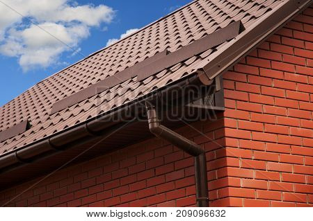 Close up on rain gutter system with downspout pipeline and metal roofing. Brick House Roof Protection from Snow Board (Snow Guard).