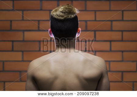 Young sporty man neck against brick wall. Mock up for tatoo.