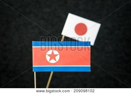 The flag of North Korea and Japan made from paper on wooden stick against dark background.