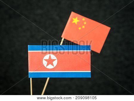 The flag of North Korea and China made from paper on wooden stick against dark background.