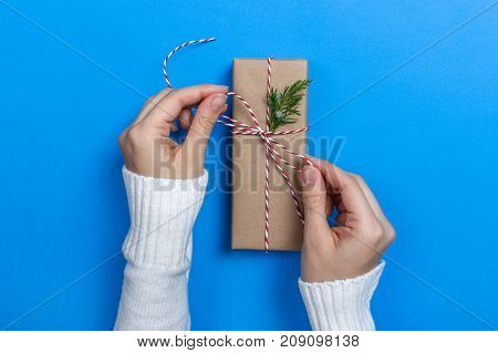 Girl hands holding present for Christmas. Packed gifts. Top view.