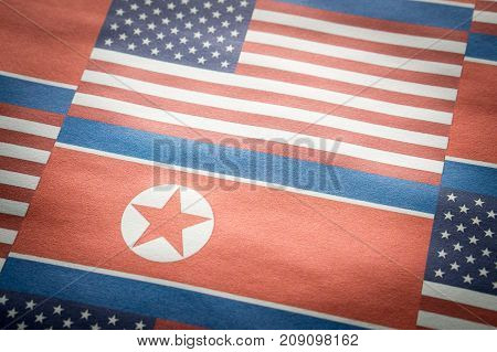 The flag of United States of America (USA) and North Korea on a wrinkled rough paper texture.