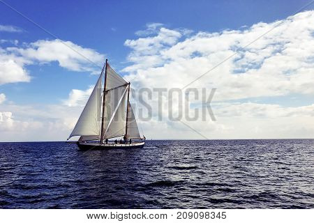 Vintage sail boat sailing on dark blue ocean under blue and cloudy sky.