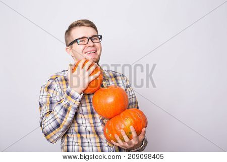 portrait of a young farmer holding a pumpkins on a light background studio.