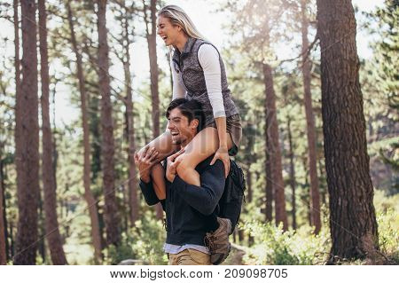 Hiking couple having fun while trekking in forest. Woman riding piggyback on man during hiking in forest.