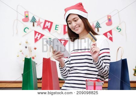 Young cute asian woman wearing Christmas hat smiling while holding tablet and credit card Christmas shopping online concept