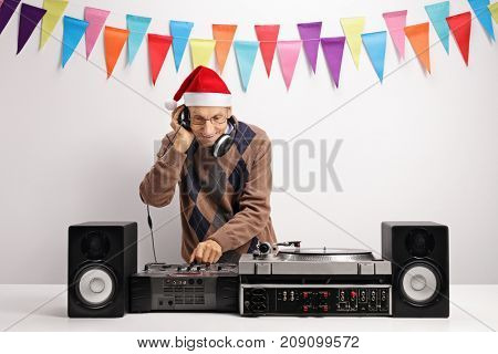 Old DJ with a christmas hat playing music against a wall with decoration flags