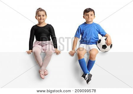 Little ballerina and a little footballer sitting on a panel isolated on white background