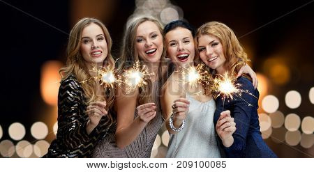 holidays, new year and people concept - happy young women with sparklers over christmas tree lights background