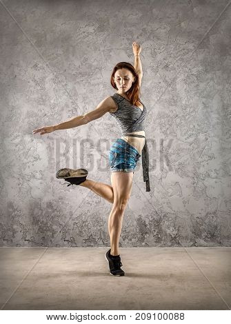Woman dancer in dynamic action on the grunge grey background.