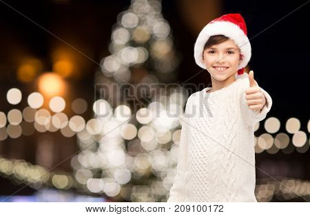holidays, gesture, childhood and people concept - smiling happy boy in santa hat showing thumbs up over christmas tree lights background