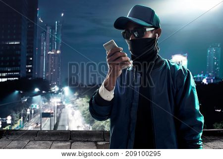 Unknown hacker use mobile phone on rooftop