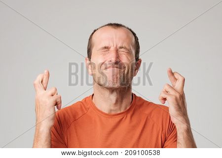 Mature hispanic man making a wish sign with crossing fingers isolated on background. He is closing eyes with strong wish