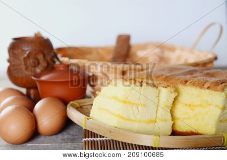 Taiwanese cheese sponge cake with bamboo weaving basket on wooden board