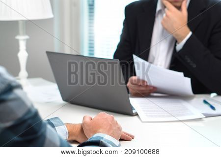 Job interview or meeting with bank worker in office. Business man considering. Discussion about loan, mortgage or insurance. Human resources conversation. Hiring or getting fired. Thoughtful man.