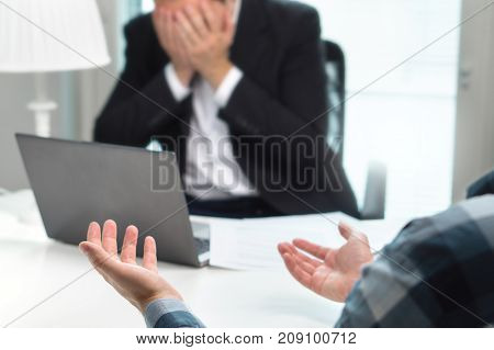 Failed job interview or business people having fight in office. Businessman covering and holding face with hands in meeting. Boss do not want to fire employee. Bad management or working environment