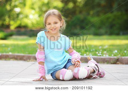 Cheerful girl on roller skates sitting in park