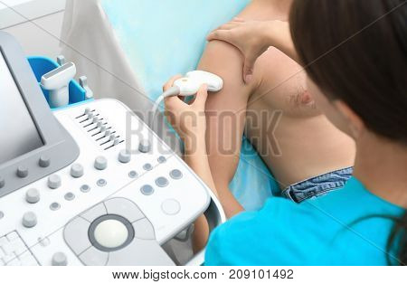 Doctor conducting ultrasound examination of patient's shoulder in clinic