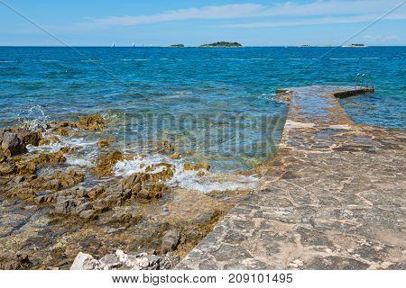Pathway on the typical rocky beach in Istria, Croatian coast. Blue transperent sea and sky.