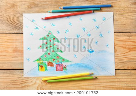Child's drawing of Christmas tree with presents on wooden background