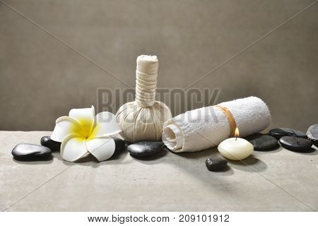 frangipani with pile of black stones and candle,towel, herbal ball ,on gray background