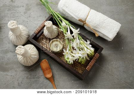 herbal ball,candle ,white flower in basket with towel ,spoon on gray background