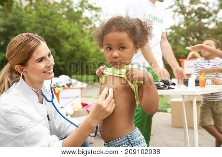 Female doctor auscultating poor African child outdoors