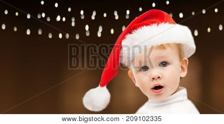christmas, holidays and people concept - little baby boy in santa hat over garland lights background