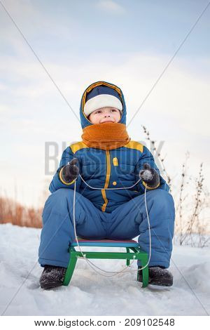 happy boy on sled in winter outdoors.