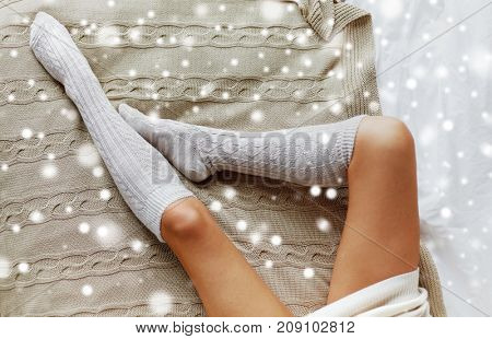winter, clothes, fashion and people concept - close up of young woman legs in knee socks on bed over snow