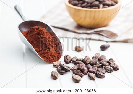 Dark cocoa powder in metal scoop and cocoa beans on white table.