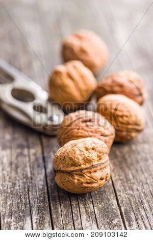 Tasty dried walnuts and nutcracker on old wooden table.