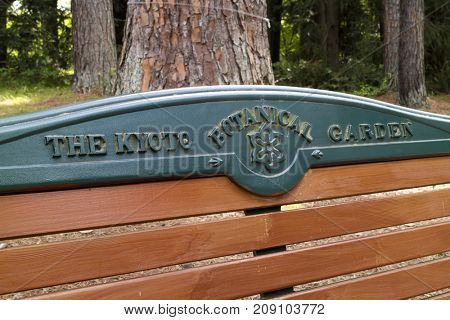 Kyoto, Japan - May 21, 2017: Name of Kyoto botanical garden on a bench in the park