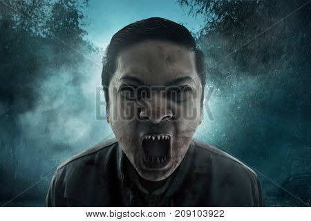 Angry vampire screaming on the forest at night