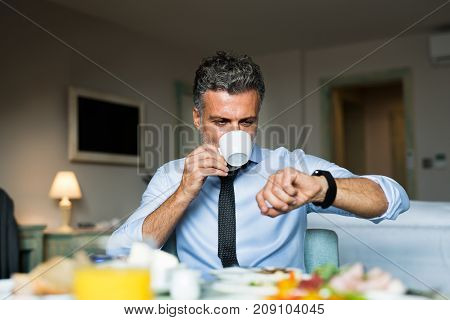 Mature, handsome businessman having breakfast in a hotel room, drinking cofee and checking time.