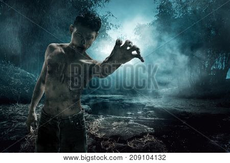 Scary zombie walking on the river at night