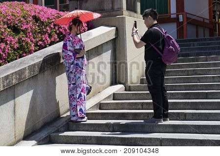 Kyoto, Japan - May 19, 2017: Traditional dressed girl in kimono with parasol is photographed at the stairs of the Yasaka jinja shrine