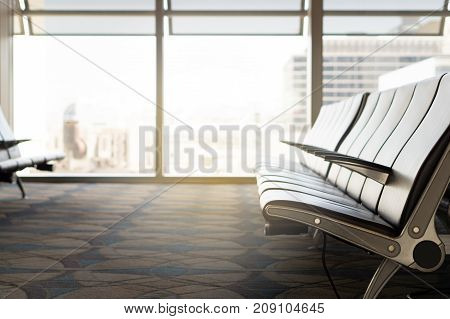 Waiting room at airport. Empty seats at gate in terminal. Light from window. Departure lounge.