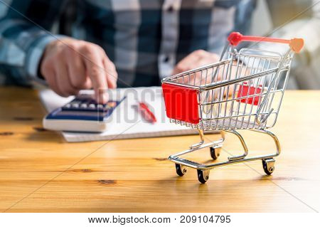 Rising food and grocery store prices and cost of living concept. Man counting food and consumer goods money with pen, paper and calculator at home. Budget of disadvantaged and low income family.