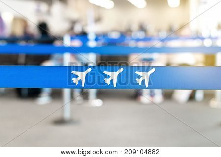 Airport waiting area, lobby or lounge. Airplane icon in queue barrier. Passengers sitting in the background. Travel and vacation concept.