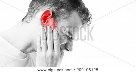 Tinnitus man on a white background holding a sick ear suffering from pain