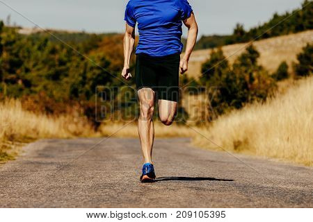 muscular legs men runner running on asphalt road in autumn field