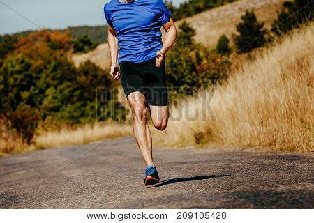 muscular athlete men runner running on asphalt road in autumn field