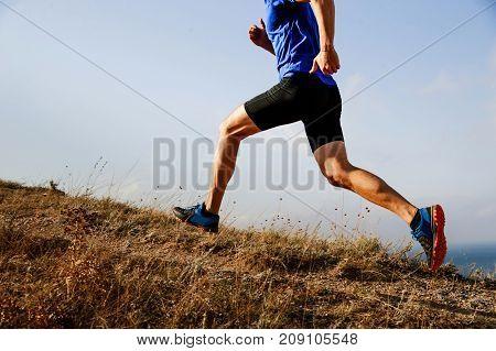 legs male athlete runner running uphill on trail background of sky