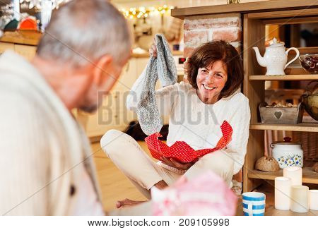 Senior couple sitting on the floor inside their house giving presents to each other, woman unwrapping her gift. Christmas time.