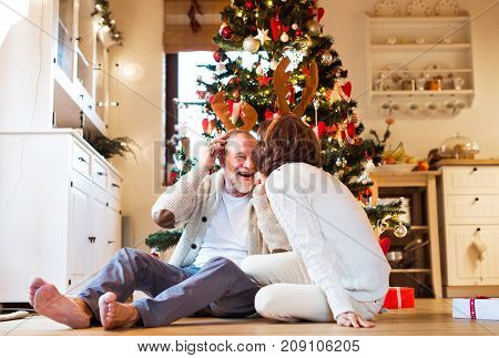 Senior couple sitting on the floor in front of illuminated Christmas tree inside their house wearing deer antlers, having fun.