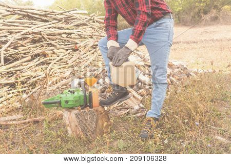 Winter is coming - lumberjack maintaining chainsaw outdoors.