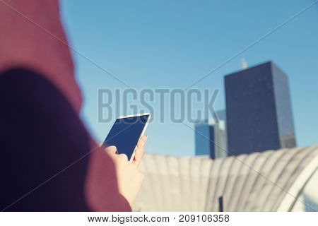 Detail of girl's hand while using touch screen on smartphone in Paris France La Defense.